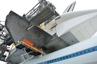 "Space shuttle Endeavour is ""soft mated"" to the Shuttle Carrier Aircraft (SCA) inside the Mate-Demate Device at the Shuttle Landing Facility at NASA's Kennedy Space Center in Florida on Sept. 14, 2012. The operation is the last of its type for t"