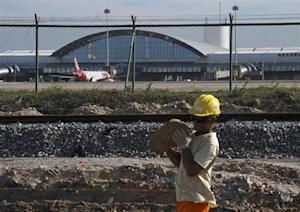 Worker carries a rock at the site of the delayed construction of a new terminal at the Pinto Martins International Airport in Fortaleza