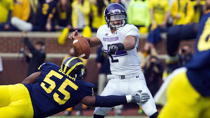 Northwestern quarterback Kain Colter (2) fumbles the ball as Michigan defensive tackle Jibreel Black (55) pressures in the second quarter of an NCAA college football game, Saturday, Nov. 10, 2012, in Ann Arbor, Mich. (AP Photo/Tony Ding)