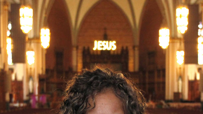 In this March 9, 2011 photo, Pam Bosley stands inside the Chicago's St. Sabina Catholic Church and poses with a photograph of her son, Terrell, who was gunned down in 2006. Bosley now works with kids 14 to 21 at the church, teaching them life and leadership skills and ways to reduce violence. Sometimes, she says, it's neglectful parents who are the problem; often it's gangs who just don't value life. (AP Photo/Charles Rex Arbogast)