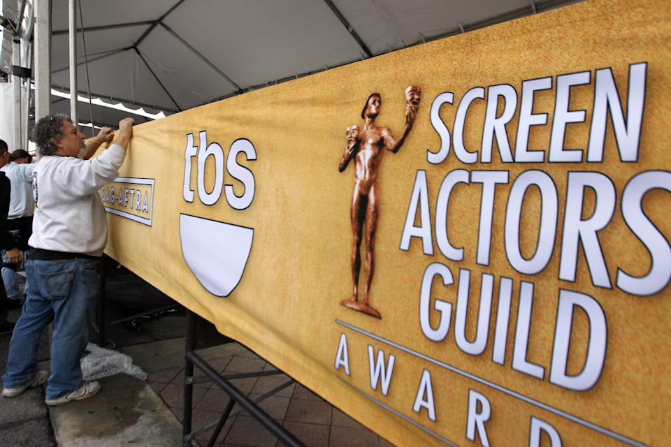 Workers set up signage on the red carpet before the 19th annual SAG Awards on Saturday, Jan 26, 2013 in Los Angeles. The SAG Awards will be held Jan. 27, 2013. (Photo by Matt Sayles/Invision/AP)