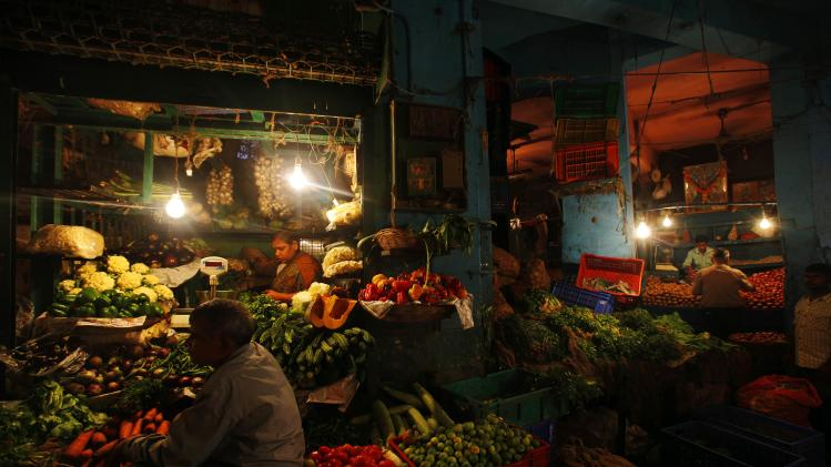 People shop at a vegetable market in Mumbai, India, Monday, Sept. 17, 2012. India's central bank, Reserve Bank of India, on Monday cut the cash reserve ratio as it tries to kick-start flagging growth and welcomed government efforts to open Asia's third-largest economy to more foreign investment. The government's announcement allowing foreign companies in retail and raising the price of diesel has met with protests from opposition parties and some of the ruling Congress party's coalition partners. (AP Photo/Rafiq Maqbool)