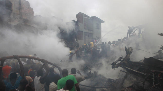 People gather at the site of a plane crash in Lagos, Nigeria, Sunday, June 3, 2012.  The passenger plane carrying more than 150 people crashed in Nigeria's largest city on Sunday, government officials said. Firefighters pulled at least one body from a building that was damaged by the crash and searched for survivors as several charred corpses could be seen in the rubble.(AP Photo/Sunday Alamba)