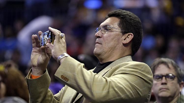 Carolina Panthers head coach Ron Rivera shoots a photo with his cell phone during the first half of an NBA basketball game between the Charlotte Bobcats and the Los Angeles Lakers in Charlotte, N.C., Friday, Feb. 8, 2013. (AP Photo/Chuck Burton)