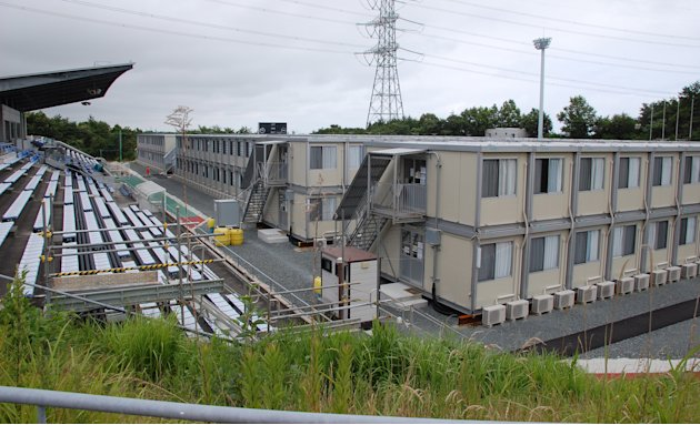 In this July 21, 2012 photo, a prefab houses are built on the football pitch at J-Village national soccer training facility for workers at the Fukushima Dai-ichi nuclear power plant in Naraha, Fukushi