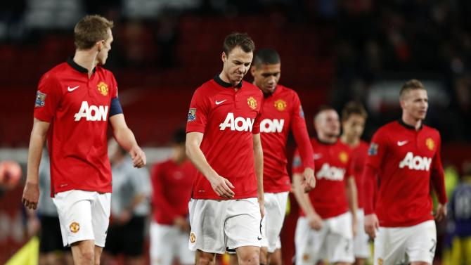 Manchester United players walk off the pitch after losing their English FA Cup soccer match against Swansea City at Old Trafford in Manchester