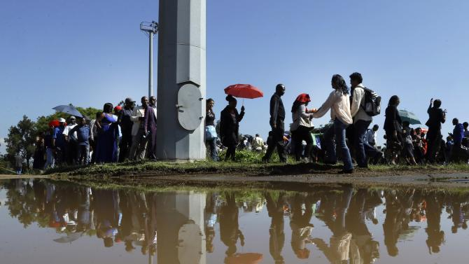 People queue to catch a bus see the remains of Nelson Mandela at the Union Buildings in Pretoria, South Africa, Thursday, Dec. 12, 2013. The body of Nelson Mandela is being take in procession to the Union Buildings in Pretoria where it will lie in state for three days. Each morning his remains will be transported from the mortuary to the government buildings. (AP Photo/Themba Hadebe)