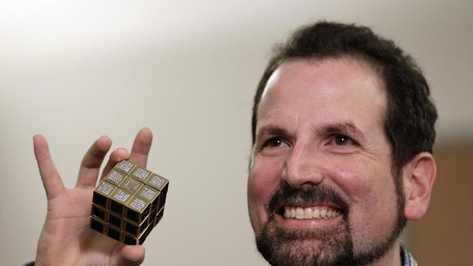 Jeweler Fred Cuellar holds a gold and gemstone version of the Rubik's Cube at Liberty Science Center, Wednesday, April 25, 2012, in Jersey City, N.J. The center will have an exhibit on the toys and will include the diamond version, which is worth 2.5 million dollars. (AP Photo/Julio Cortez)
