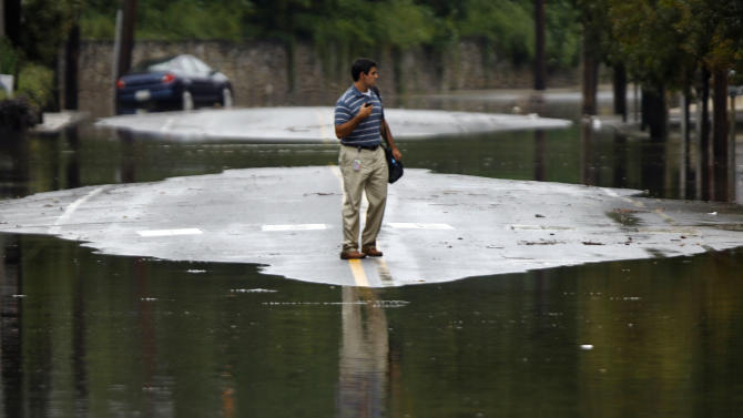 A person turns back from crossing floodwaters, Thursday, Sept. 8, 2011, in the Manayunk neighborhood of Philadelphia. Widespread flooding brought on by the remnants of Tropical Storm Lee was being blamed for two deaths in Pennsylvania, where inundated communities were evacuated and state offices closed down on Thursday because of the rising waters. (AP Photo/Matt Rourke)
