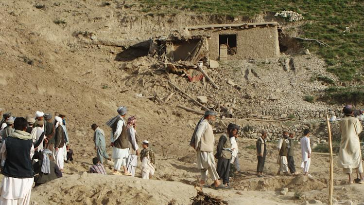 Afghans stand at the site after an earthquake hit Baghlan province, north of Kabul, Afghanistan, Monday, June 11, 2012. As many as 100 people are feared dead after an earthquake struck northern Afghanistan this morning. The governor of Baghlan province says the quake triggered a landslide that buried a remote village under mud and rocks. He says rescuers have so far pulled two bodies from the rubble, while the U.N. confirms one other death. The world body says houses were destroyed across five districts in all. (AP Photo/Jawed Basharat)