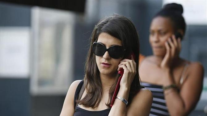Women use their mobile phones in central London August 30, 2013.