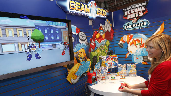 Demonstrator Sharon Juchniewicz plays the TRANSFORMERS RESCUE BOTS BEAM BOX game in Hasbro's showroom at the American International Toy Fair, Friday, Feb. 8, 2013, in New York.  Interactive missions packed with lights, sounds and signature TRANSFORMERS RECUE BOTS character voices transport kids into an adventurous world of gameplay and mini-missions this fall. (Photo by Jason DeCrow/Invision for Hasbro/AP Images)