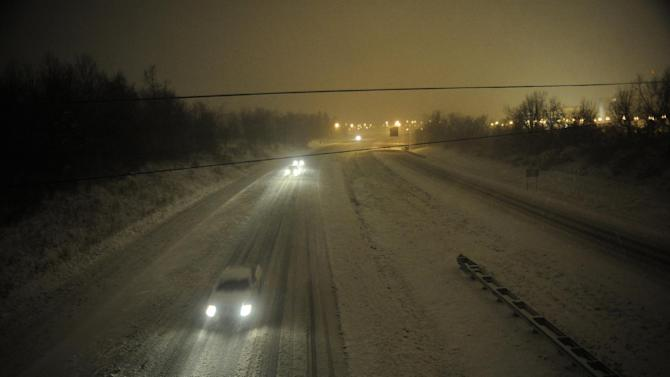Motorists travel slowly on a snow-covered Interstate 24 during a winter storm Wednesday, December 26, 2012, in Paducah, Ky. The storm dumped several inches of snow making travel hazardous. (AP Photo/Stephen Lance Dennee)