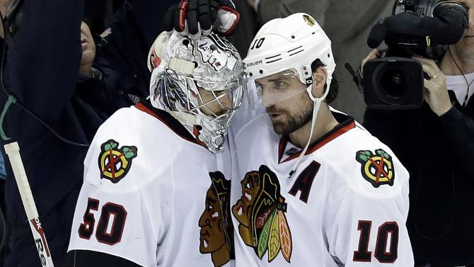 Chicago Blackhawks goalie Corey Crawford (50) is congratulated by Chicago Blackhawks center Patrick Sharp (10) after beating the Detroit Red Wings 4-3 after Game 6 of the Western Conference semifinals in the NHL hockey Stanley Cup playoffs in Detroit, Monday, May 27, 2013. (AP Photo/Paul Sancya)
