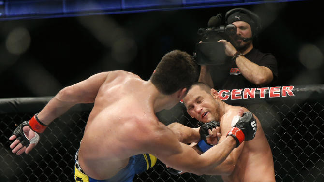 Lyoto Machida, left, of Brazil, kicks Dan Henderson during their UFC 157 light heavyweight mixed martial arts match in Anaheim, Calif., Saturday, Feb. 23, 2013. Machida won by split decision after the third round. (AP Photo/Jae C. Hong)