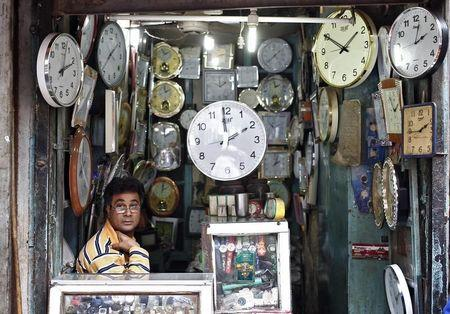 A shopkeeper waits for customers at his shop selling wall clocks in Delhi