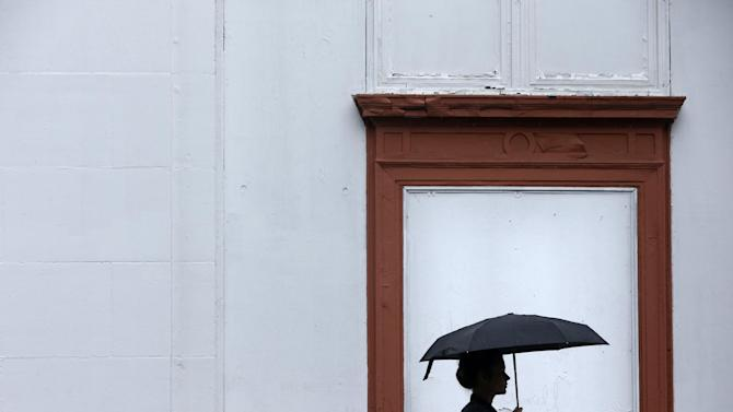 A woman walks shielded from a rainstorm with an umbrella, Friday, June 7, 2013, in Philadelphia. The National Weather Service has issued a flash flood watch for much of southeastern Pennsylvania as remnants of Tropical Storm Andrea move through the region. (AP Photo/Matt Rourke)