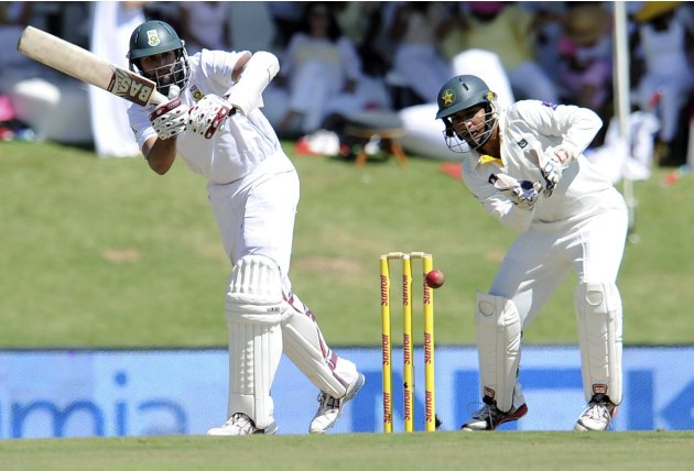 South Africa's Hashim Amla plays a shot as Pakistan's wicketkeeper Sarfraz Ahmed looks on during the first day of the third cricket test match in Pretoria