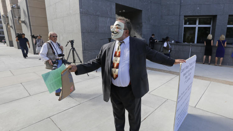 A masked demonstrator hands out literature in front of federal court where the trial of former Virginia Gov. Bob McDonnell  is being held Wednesday, Aug. 20, 2014,  in Richmond, Va. The demonstrator who declined to give out his name, protested the greed of the former governor and his wife. The  defense continues to present its case in the McDonnell's corruption case.  (AP Photo/Steve Helber)