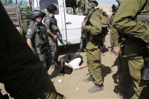 French diplomat Castaing lays on the ground after Israeli soldiers carried her out of her truck containing emergency aid, in the Jordan Valley