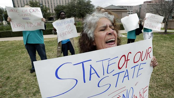 FILE - In this Jan. 29, 2013 file photo, Maria Webster joins others protesting Texas Gov. Rick Perry's stance on health care outside the state capitol in Austin, Texas, where Perry was to deliver the state of the state address. Three years, two elections, and one Supreme Court decision after President Barack Obama signed the Affordable Care Act, its promise of health care for the uninsured may be delayed or undercut in much of the country because of entrenched opposition from many Republican state leaders.  (AP Photo/Eric Gay, File)