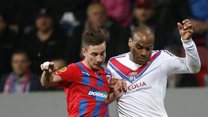 Viktoria Plzen's Milan Petrzala, left,  challenges Lyon's Jimmy Briand, right, during their Europa League second leg round of 16 soccer match in Pilsen, Czech Republic, Thursday, March 20, 2014