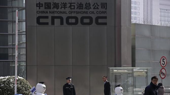 Security personnel stand next to snowmen at the entrance of China National Offshore Oil Corp office tower in Beijing