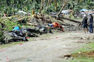 Residents look at deceased victims of flash floods caused by Typhoon Bopha in New Bataan on December 8. Desperate families begged for food Sunday, days after the typhoon brought death and destruction to parts of a southern Philippine island