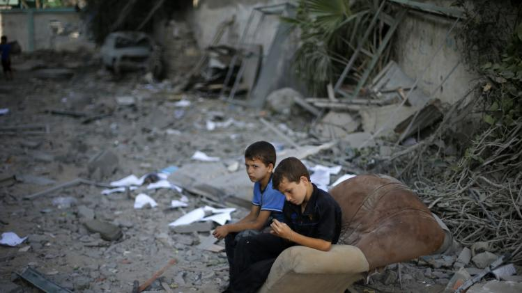 Palestinian boys sit on a sofa outside their house in Gaza City
