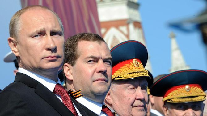 Russian President Vladimir Putin, left, and Prime Minister Dmitry Medvedev attend a Victory Day parade, which commemorates the 1945 defeat of Nazi Germany, at Red Square in Moscow, Russia, Friday, May 9, 2014. Russia marked the Victory Day on May 9 holding a military parade at Red Square. (AP Photo/RIA-Novosti, Mikhail Klimentyev, Presidential Press Service)