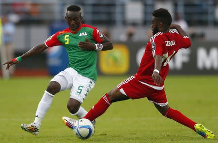Senobua of Equatorial Guinea fights for the ball with Burkina Faso's Koffi during their Group A soccer match at the African Cup of Nations in Bata