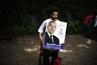 A supporter of Egyptian presidential candidate and former prime minister Ahmed Shafiq holds his poster during a press conference in Cairo