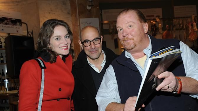 IMAGE DISTRIBUTED FOR FOOD & WINE - Mario Batali, right, shows off his guest-edited April issue of FOOD & WINE to actor Stanley Tucci, center, and wife Felicity Blunt during a party at Eataly in New York, Wednesday, March 6, 2013.  (Photo by Diane Bondareff/Invision for FOOD & WINE/AP Images)