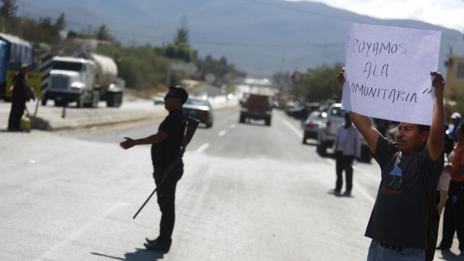 A member of the Community Police from the FUSDEG directs traffic as a villager holds up a sign in support of the group at an entry to Petaquillas