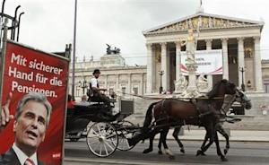 A traditional Fiaker carriage passes an election poster of Austrian Chancellor Faymann of the social democrats (SPOe) in front of the parliament in Vienna