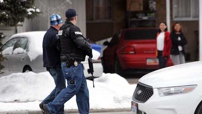 """Unified Police Department officers patrol a Midvale, Utah neighborhood after a shooting Tuesday, Feb. 12, 2013. Three people were shot to death and one was critically wounded at a known drug house in suburban Salt Lake City, causing temporary lockdowns at several area schools as police looked for two men who may have been involved. Investigators said a person inside the house reported the shooting in Midvale at about 8 a.m. Unified Police Department Lt. Justin Hoyal said a search warrant had been served at the house in recent weeks for drug activity. """"It was a known narcotics house,"""" he said. (AP Photo/The Deseret News, Jeffrey D. Allred)  SALT LAKE TRIBUNE OUT;  MAGS OUT"""