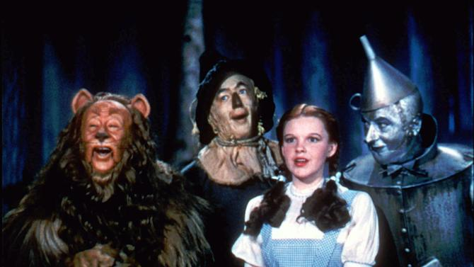 """FILE - In this undated file photo provided by Warner Bros., Bert Lahr as the Cowardly Lion, Ray Bolger as the Scarecrow, Judy Garland as Dorothy, and Jack Haley as the Tin Woodman, sing in this scene from """"The Wizard of Oz,"""" distributed by Warner Bros. On Sunday, Nov. 11, 2012, auction house Julien's Auctions said the blue pinafore dress that Garland wore in the movie fetched the highest price of any item during a two-day auction of Hollywood memorabilia that attracted bids from around the world, selling for $480,000. (AP Photo/Warner Bros., File) NO SALES"""