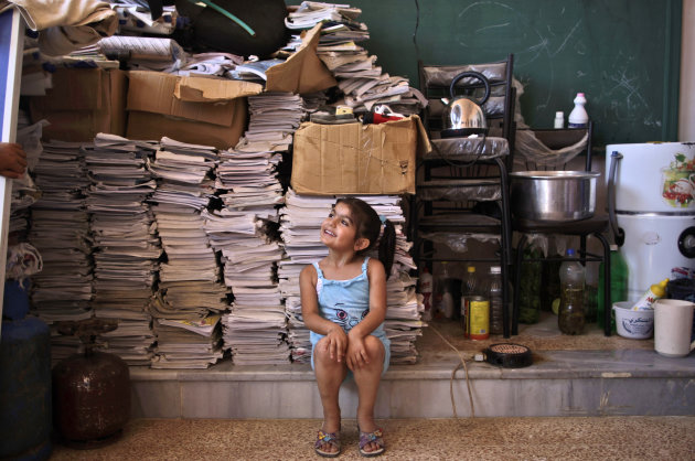Syrian girl, Sana Mustafa, 5, who fled her home in Anadan with her family due to fighting between the rebels and the Syrian army, talks with her brother Riyyad, in a school where she and her family took refuge, in Kafar Hamra, on the outskirts of Aleppo, Syria, Wednesday, Aug. 22, 2012. (AP Photo/Muhammed Muheisen)