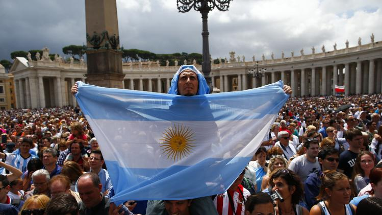 A man holds an Argentine national flag as Pope Francis leads his Sunday Angelus prayer in Saint Peter's square at the Vatican