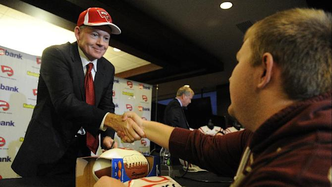 """New Western Kentucky head coach Bobby Petrino, left, shakes hands with student Jared Willis at an NCAA college football news conference, Monday, Dec. 10, 2012, in Bowling Green, Ky. The 51-year-old was fired by Arkansas in April for a """"pattern of misleading"""" behavior following an accident in which the coach was injured while riding a motorcycle with his mistress as a passenger but now wants to make the most of his second chance. (AP Photo/The Daily News, Joe Imel)"""