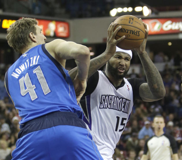 Sacramento Kings center DeMarcus Cousins, right, goes to the basket against Dallas Mavericks forward Dirk Nowitzki, of Germany, during the third quarter of an NBA basketball game in Sacramento, Calif.