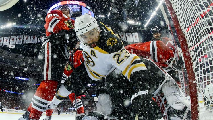 AP10ThingsToSee - Boston Bruins center Chris Kelly (23) trips over Chicago Blackhawks goalie Corey Crawford, who blocked his shot, in the first period of Game 5 of the NHL hockey Stanley Cup Finals, Saturday, June 22, 2013, in Chicago. (AP Photo/Bruce Bennett, Pool, File)