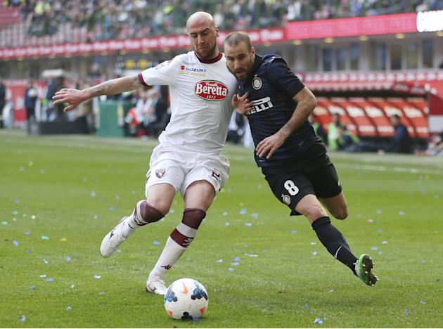 Inter Milan forward Rodrigo Palacio, right, of Argentina, challenges for the ball with Torino defender Guillermo Rodriguez, of Uruguay, during the Serie A soccer match between Inter Milan and Torino a