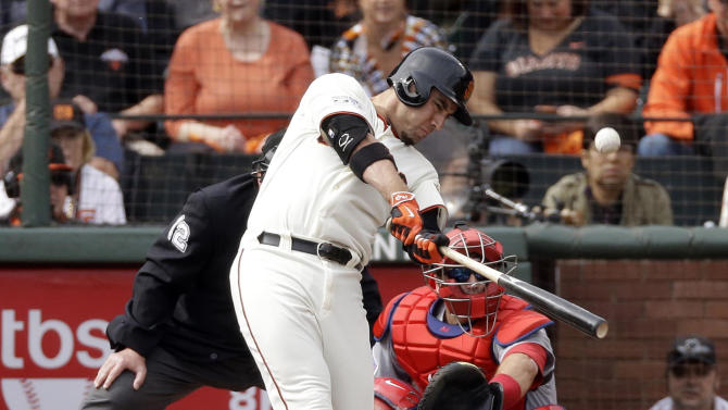 FILE - In this Oct. 14, 2014, file photo, San Francisco Giants' Travis Ishikawa hits a three run double against the St. Louis Cardinals during the first inning of Game 3 of the National League baseball championship series in San Francisco. Viewers tuning into the National League Championship Series on Fox Sports 1 saw an ad behind the batter promoting the ALCS on TBS, and vice versa. Sure, they're helping the competition, network executives say. They also believe they're helping themselves. (AP Photo/Jeff Chiu, File)