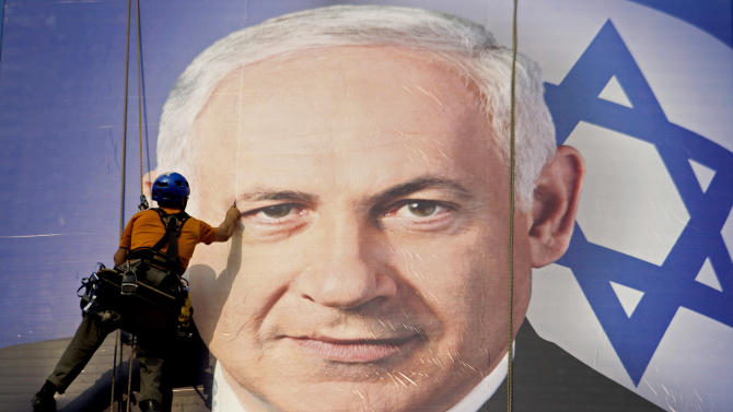 FILE - In this Thursday, Jan. 17, 2013 file photograph, a worker hangs a huge poster with an image of Israel's Prime Minister Benjamin Netanyahu overlooking the Ayalon freeway in Tel Aviv, Israel. After a lackluster three-month campaign, there seems to be little doubt that Prime Minister Benjamin Netanyahu is on his way to re-election. But the makeup of Netanyahu's next government remains a matter of great uncertainty. (AP Photo/Ariel Schalit, File)