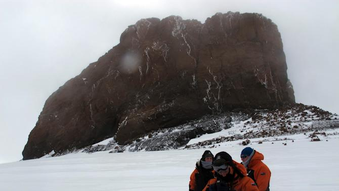 """This Jan. 20, 2013 photo shows tourists near Castle Rock on Crater Hill on Ross Island, Antarctica. Tourism is rebounding here five years after the financial crisis stifled what had been a burgeoning industry. And it's not just retirees watching penguins from the deck of a ship. Visitors are taking tours inland and even engaging in """"adventure tourism"""" like skydiving and scuba diving under the ever-sunlit skies of a Southern Hemisphere summer. (AP Photo/Rod McGuirk)"""