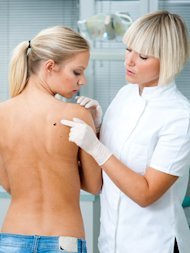dermatologist examining patient's skin