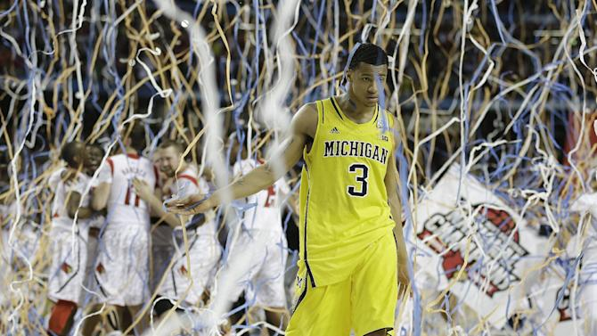 Michigan guard Trey Burke (3) walks off the court as Louisville celebrate their win during the second half of the NCAA Final Four tournament college basketball championship game Monday, April 8, 2013, in Atlanta. Louisville won 82-76. (AP Photo/Charlie Neibergall)