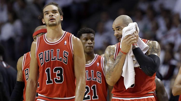 Chicago Bulls' Carlos Boozer  wipes his face as he stands with Joakim Noah (13) during a time out in the first half against the Miami Heat in Game 5 of an NBA basketball Eastern Conference semifinal, Wednesday, May 15, 2013, in Miami. (AP Photo/Wilfredo Lee)