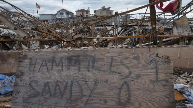 "FILE - In this Saturday, Nov. 24, 2012 file photo, a sign which reads, ""Hammills: 1 Sandy: 0, We'll be back bigger, stronger,"" stands in the rubble next to the ruins of a home in the Breezy Point section of the Queens borough of New York. A fire destroyed more than 100 homes in the oceanfront community during the storm. Sandy was only the second tropical system starting with an ""S'' to have its name retired, an indication of how unusual it is to have potent late season storms and how busy 2012 was for Atlantic storms. (AP Photo/Mark Lennihan)"